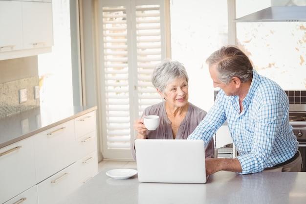 キッチンで相互作用する年配のカップル