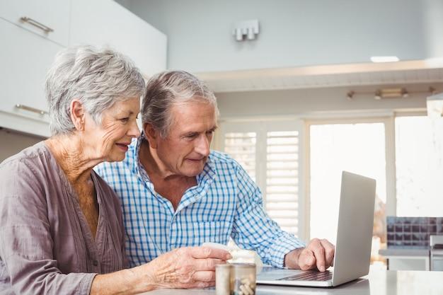 ラップトップを使用して薬と年配のカップル