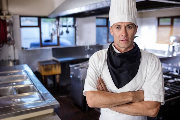Мужской шеф-повар, стоя со скрещенными руками на кухне
