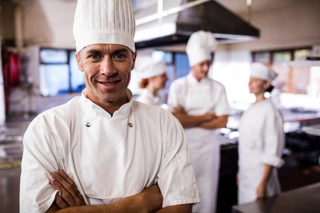 同僚がキッチンで相互作用しながら腕を組んで立っている男性シェフ