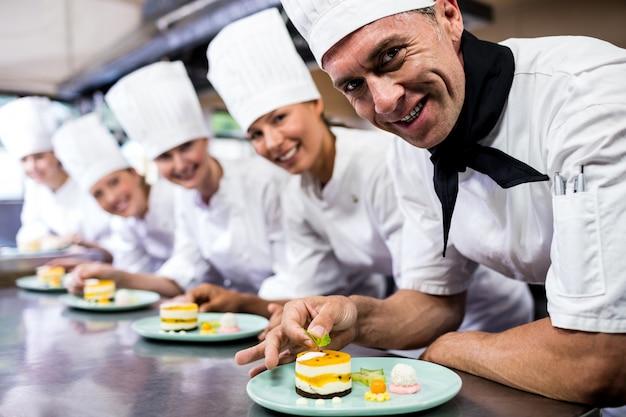 Группа поваров, гарнир вкусные десерты в тарелку