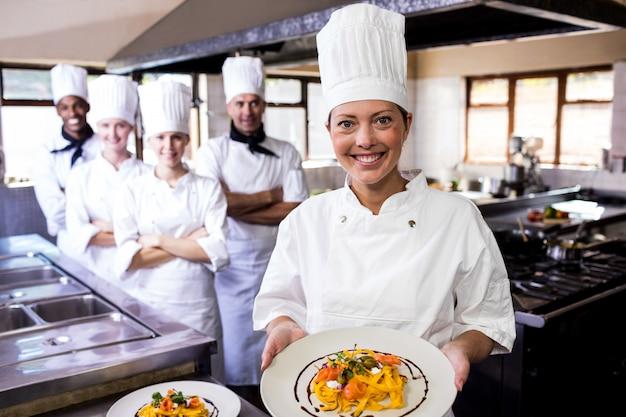 Группа поваров, держа тарелку готовых макарон в кухне