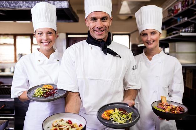 キッチンで調理済み食品のプレートを保持しているシェフのグループ