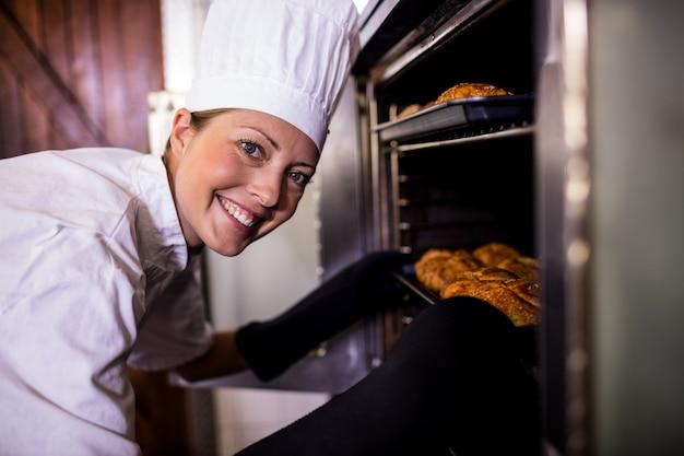Женщины-повара ставят в духовку противень из кайзера