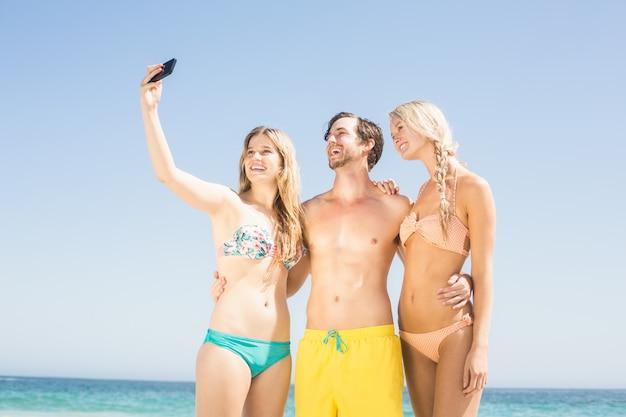 Молодые друзья, принимая селфи на пляже