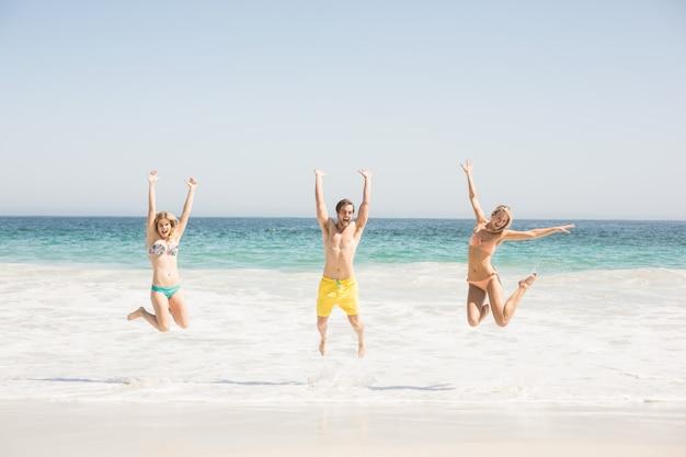 幸せな若い友達がビーチでジャンプ