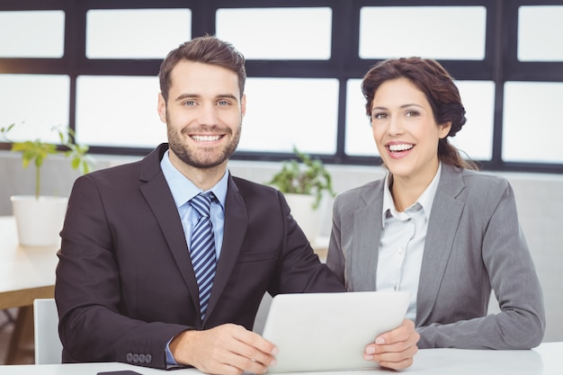 オフィスでデジタルタブレットを持つ幸せなビジネス人々