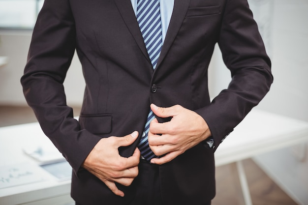 Бизнесмен, регулируя костюм, стоя в офисе