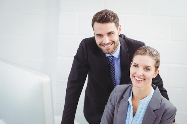 コンピューターのデスクで幸せなビジネス人々
