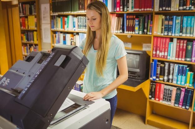 Улыбающаяся блондинка студент делает копию в библиотеке