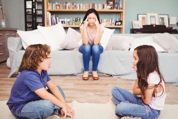 母親がソファに座って遊んでいる子供たち