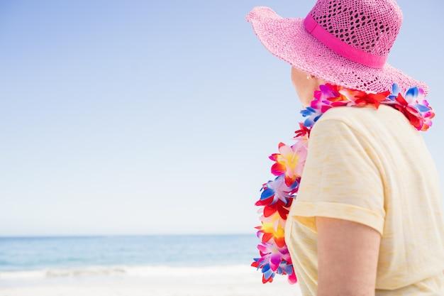 年配の女性がビーチを見て