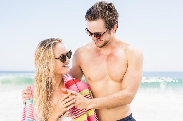 ビーチで抱きしめるサングラスの若いカップル