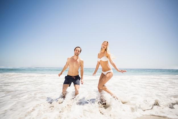 海岸の水で楽しんで幸せなカップル