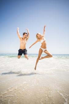 幸せなカップルがビーチでジャンプ