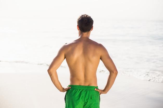 ビーチに立っている水泳パンツの男の背面図