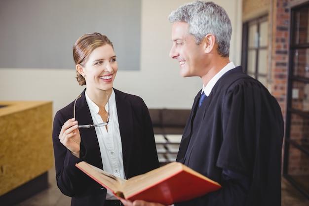 女性の同僚によって立っている幸せな男性弁護士