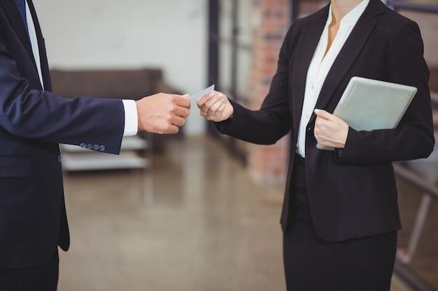 Коммерсантка давая визитную карточку клиенту в офисе
