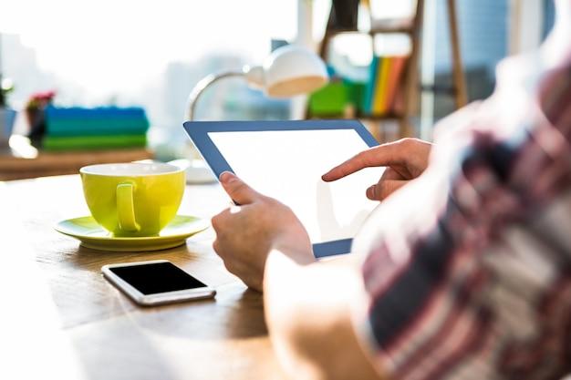 オフィスでタブレットを使用して流行に敏感なビジネスマンの画像をトリミング