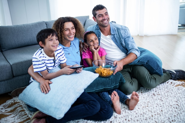 テレビでアメリカンフットボールの試合を見ている家族