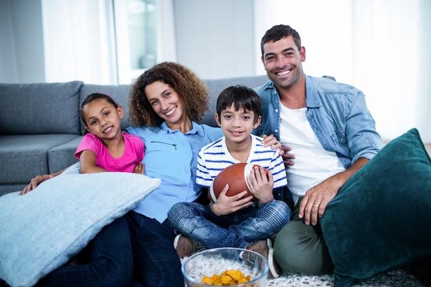 テレビでアメリカンフットボールの試合を見ている家族の肖像画