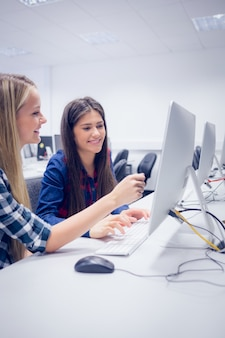 大学でコンピューターに取り組んでいる笑顔の子供達