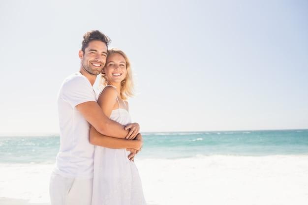 若いカップルを抱いて笑顔