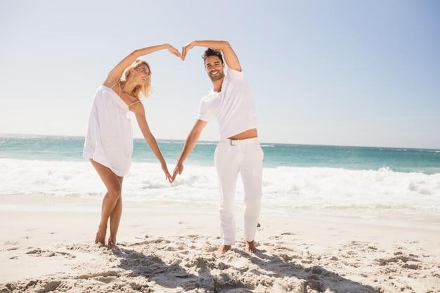 Улыбающаяся молодая пара делает форму сердца