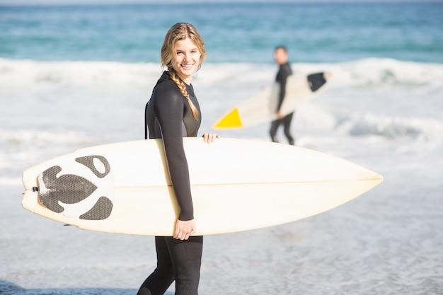 サーフボードとビーチの上を歩くサーファー