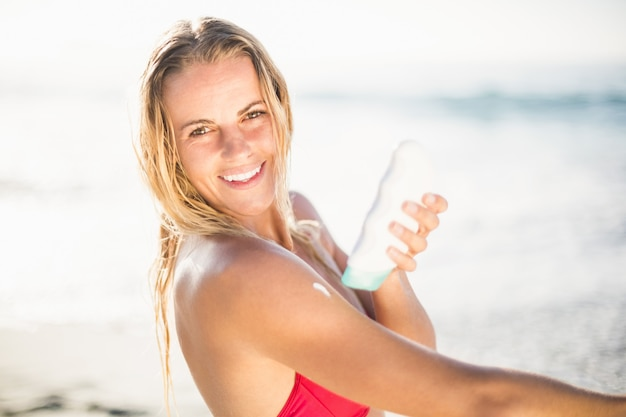 ビーチで日焼け止めローションを適用する幸せな女の肖像