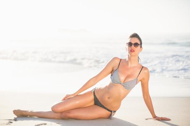 ビーチに座っている魅力的な女性