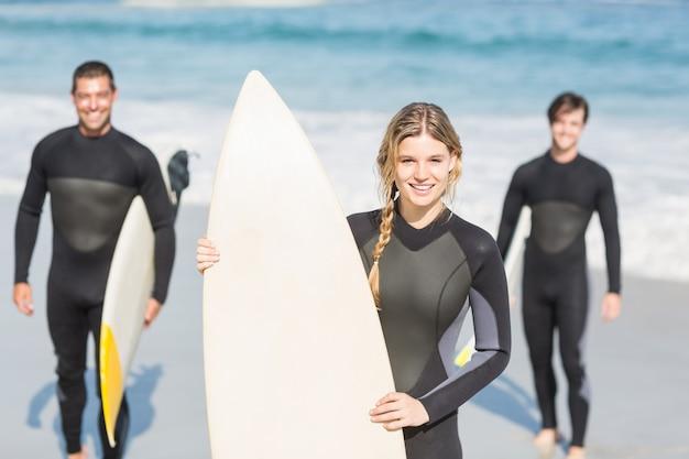 ビーチに立っているサーフボードとサーファーの友人の肖像画