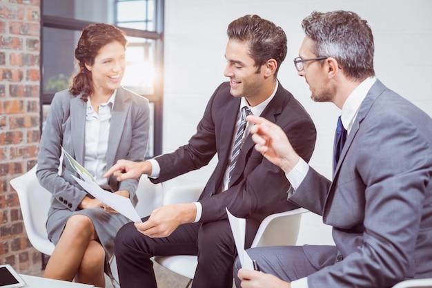 椅子に座ってドキュメントを保持している幸せなビジネス人々