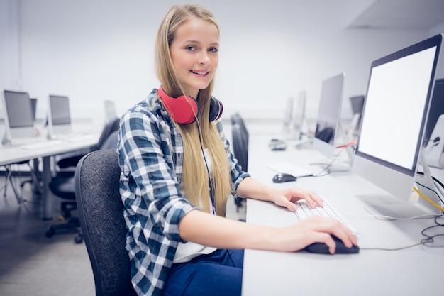 大学でコンピューターに取り組んでいる笑顔の学生