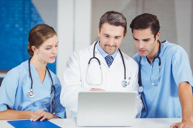 Концентрированные врачи, используя ноутбук, стоя за столом