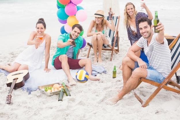 ビーチでビール瓶を乾杯の友人のグループ