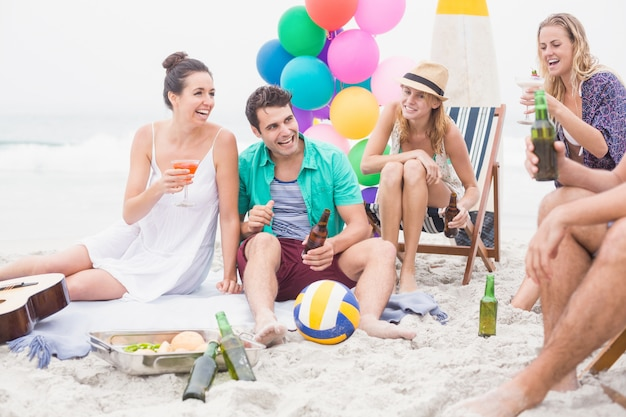 ビーチで一緒に楽しんで飲み物と友人のグループ