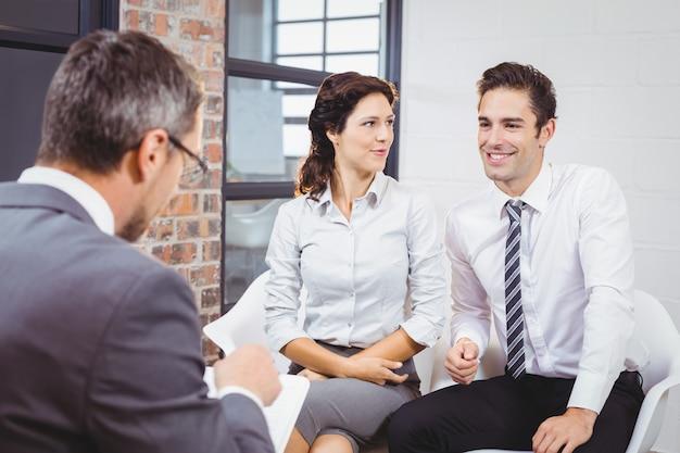 笑顔のクライアントと議論するビジネスプロフェッショナル