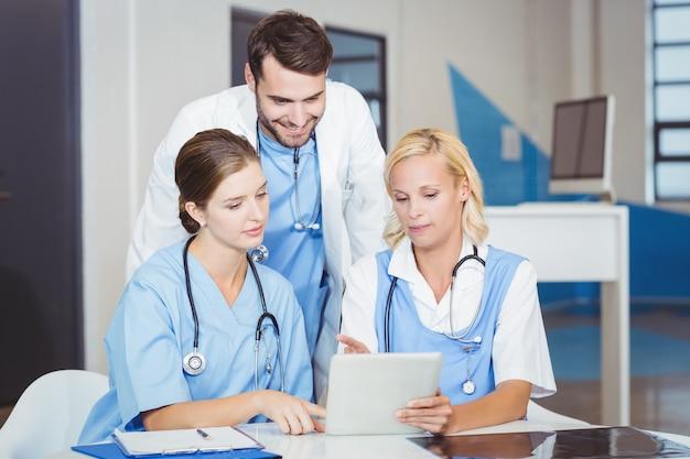 同僚と議論しながらデジタルタブレットを使用して女性医師