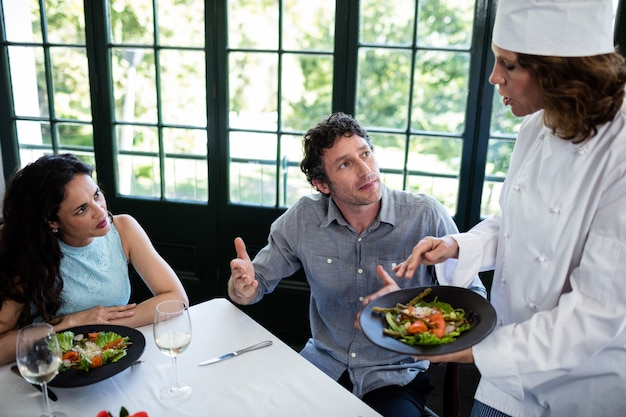 シェフに食べ物について不平を言っているカップル