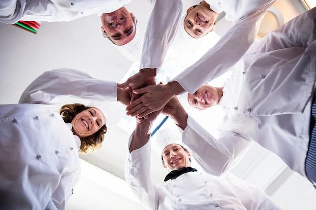 手を組んで応援するシェフチームの肖像画