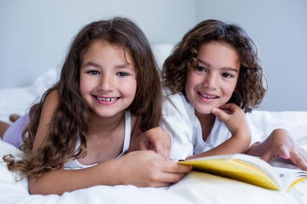 Портрет брата и сестры, читая книгу вместе на кровати