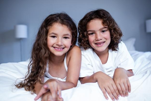 Портрет брата и сестры, лежа на кровати