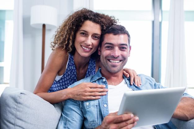 ソファの上にデジタルタブレットを使用して若いカップルの肖像画