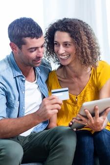 デジタルタブレットでオンラインショッピングを行うカップル