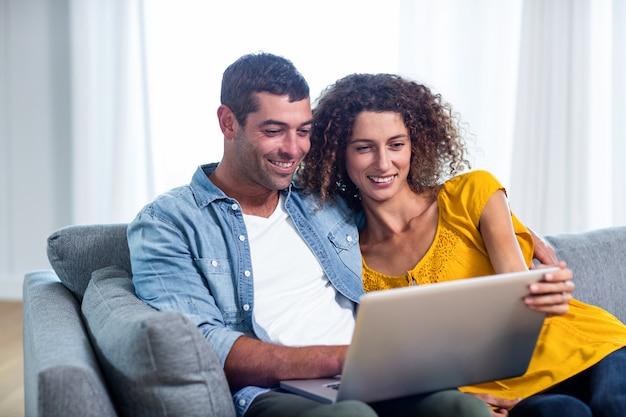 Молодая пара сидит на диване и с помощью ноутбука
