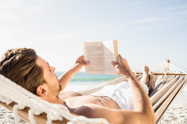 Человек читает книгу в гамаке