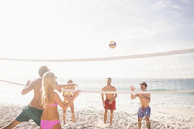 ビーチバレーボールを遊んで幸せな友達