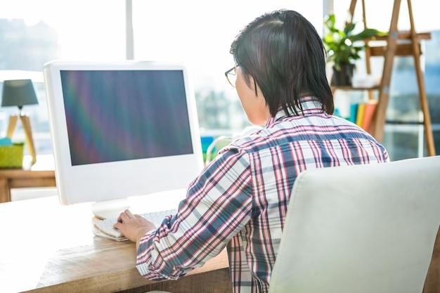 実業家のオフィスでコンピューターを使用しての背面図
