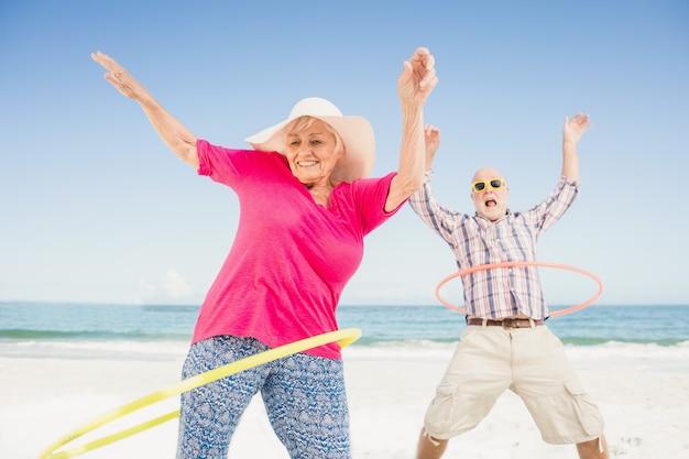フラフープをしている年配のカップル